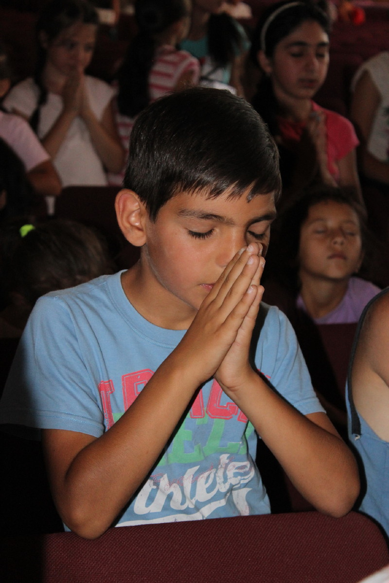 Young boy from Central Asia praying