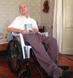 Elderly Ukrainian man with Scripture and a wheelchair