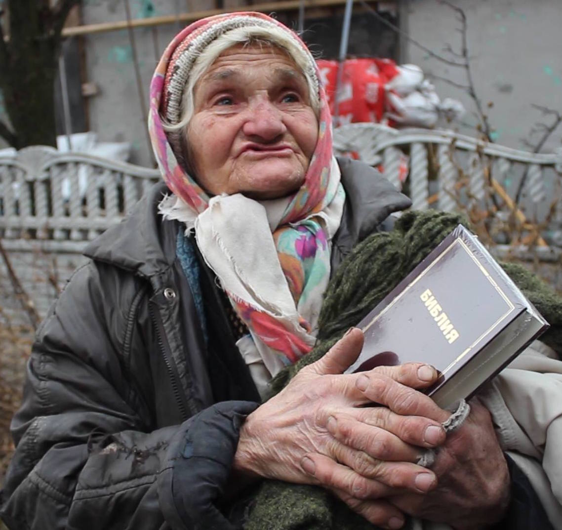 Elderly refugee woman holding a Bible in eastern Ukraine