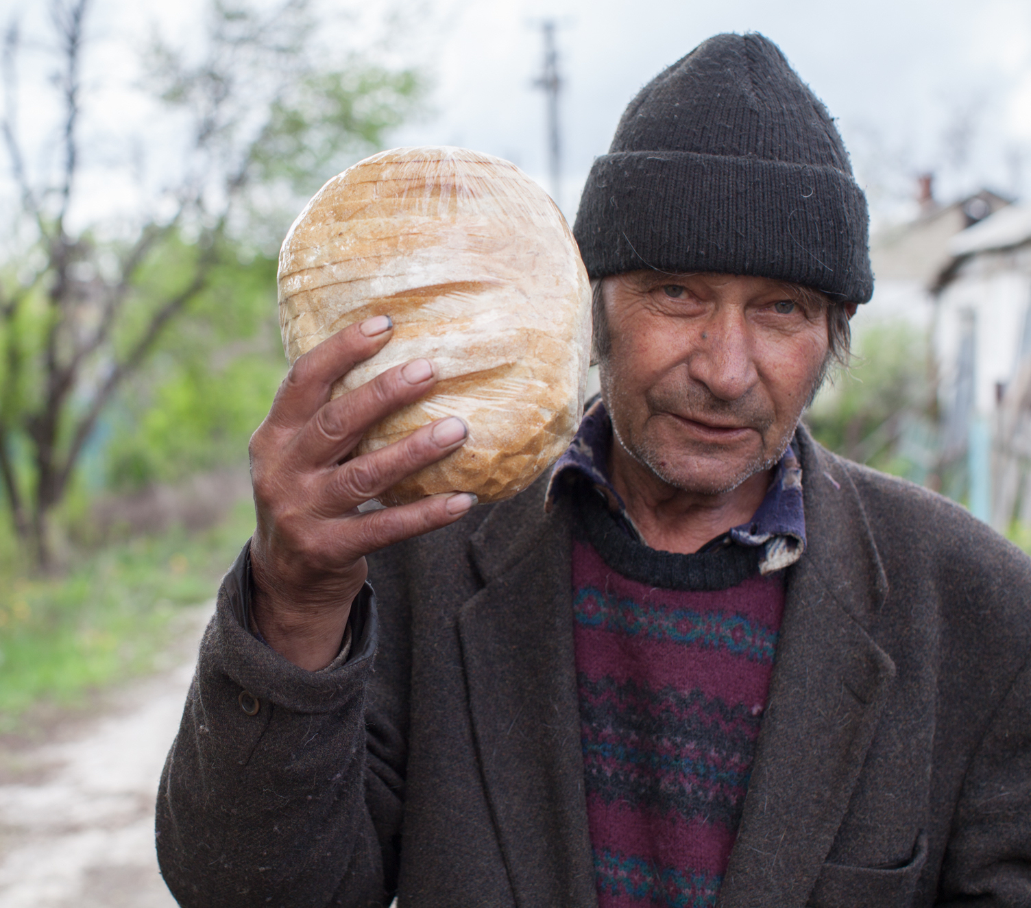 Refugee man from eastern Ukraine holding a loaf of bread