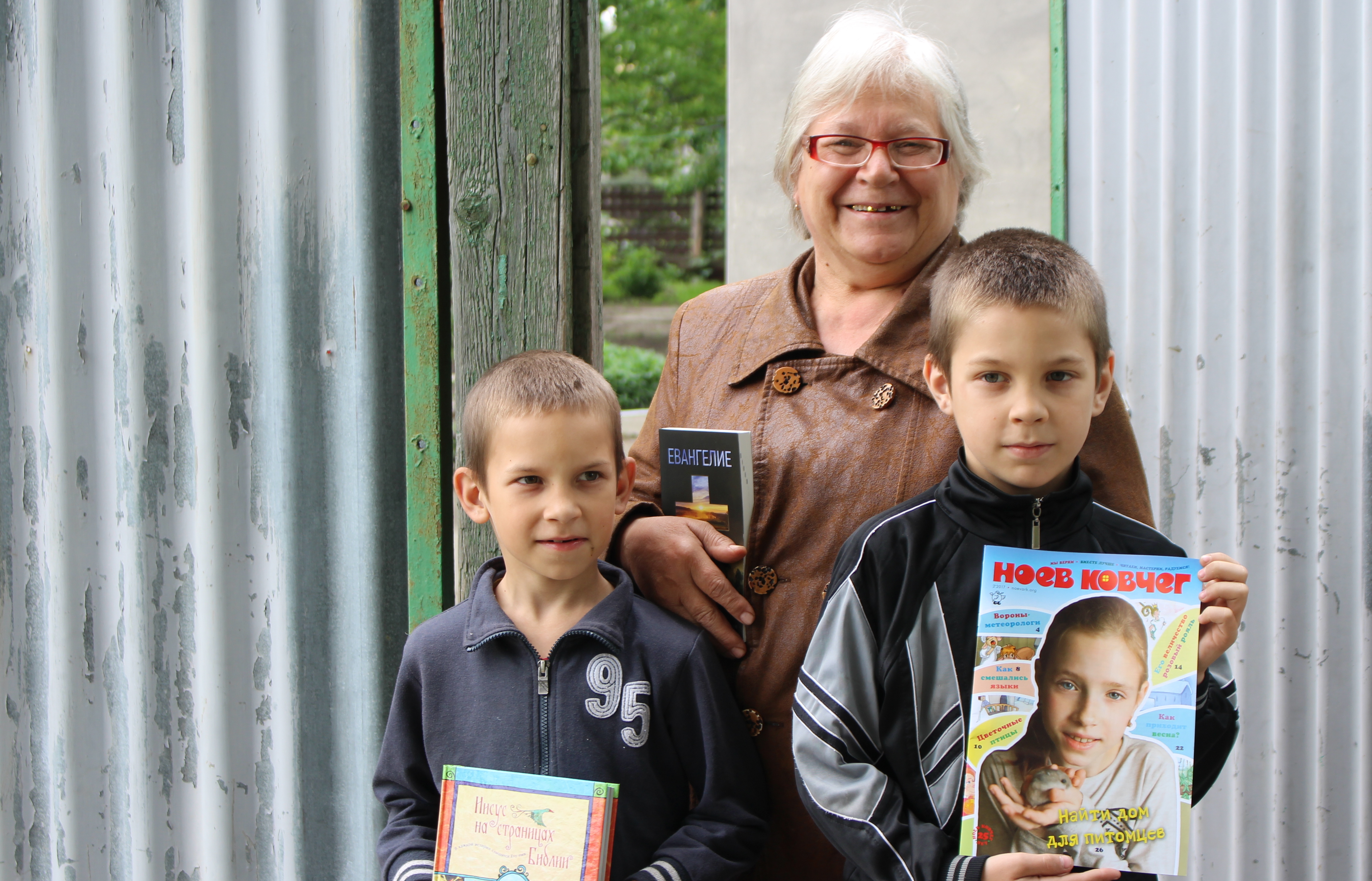 Grandma and grandsons holding Scripture pieces