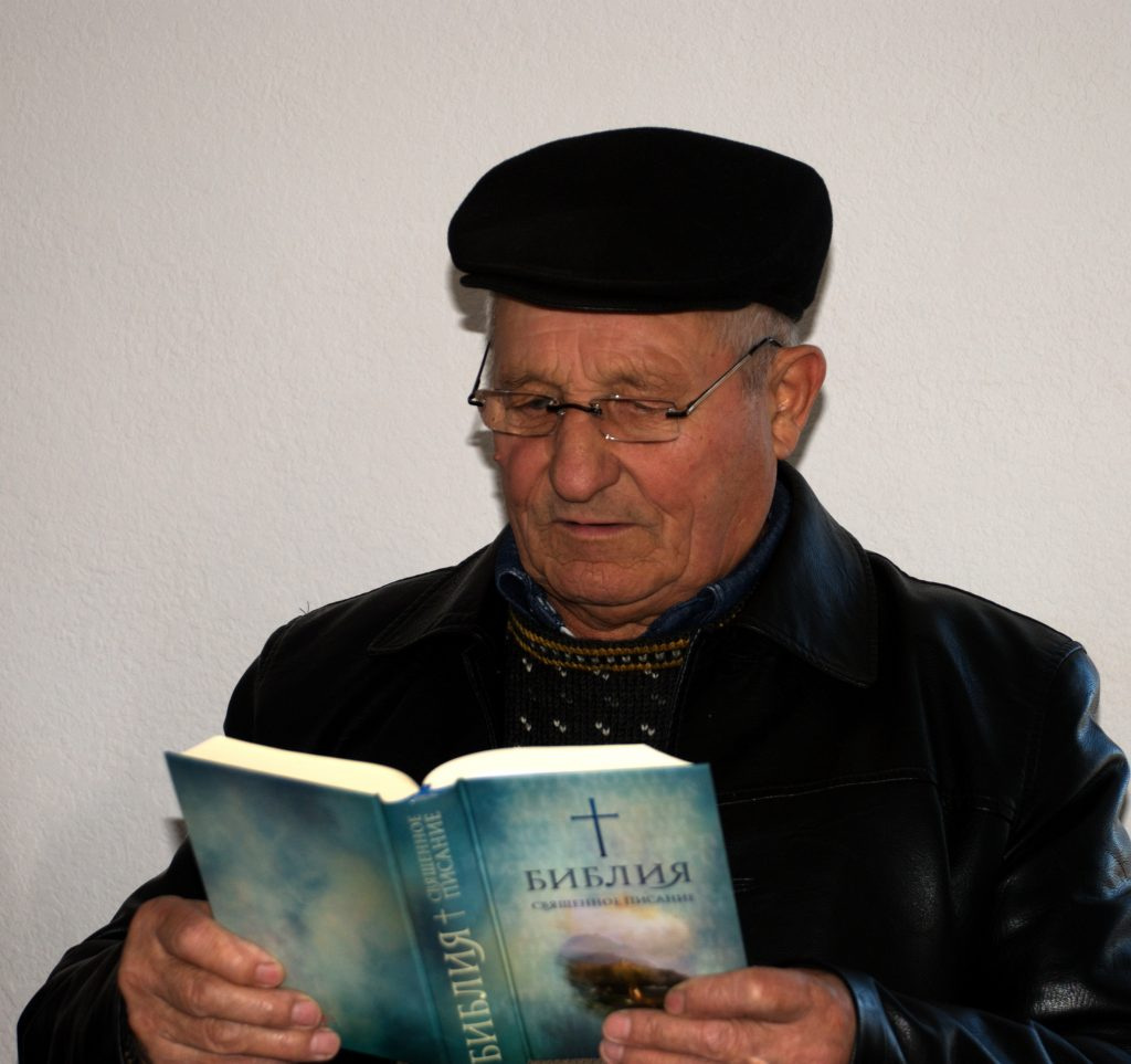 Ukrainian man with eyeglasses reading Scripture